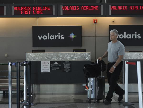 A airline passenger at Denver International Airport, rolls his luggage past the Volaris ticket counter Friday afternoon exiting a ticket counter from another airline. Volaris will greet it's first non-stop flight from Mexico City Saturday, December 8th, 2012 at DIA. The Denver Post/ Andy Cross